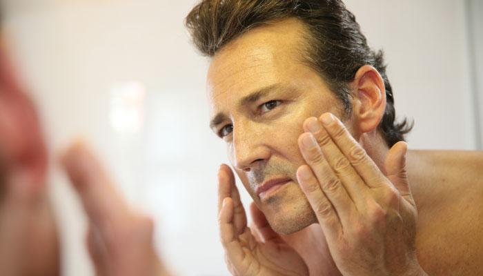 older-guy-examines-face-700x400